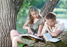 The guy and the girl prepare for examinations. Young guy and the girl with textbooks on the bank of lake Stock Photo