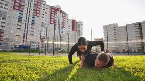Guy and girl push-ups outdoors. Male and female doing exercises together outdoor. Couple doing sport keeping the body in. Tension, leaning on the extended arms stock video footage