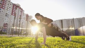 Guy and girl push-ups outdoors. Male and female doing exercises together outdoor. Couple doing sport keeping the body in. Tension, leaning on the extended arms stock footage