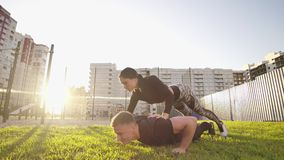 Guy and girl push-ups outdoors. Male and female doing exercises together outdoor. Couple doing sport keeping the body in. Tension, leaning on the extended arms stock video