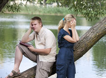 The guy and the girl in quarrel on the bank of the lake Stock Photo