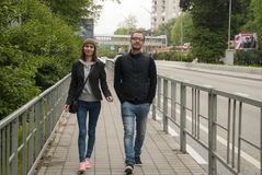 A guy and a girl quickly walk down the street Stock Photo