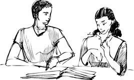 Guy and a girl reading a book at the table Royalty Free Stock Image