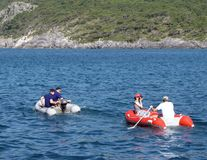 A guy with a girl in a red inflatable boat rowing on the sea. Rescue means from the equipment of a cruise yacht. Dingy. Rest on th. E water in a clear sunny warm royalty free stock photo