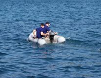 A guy with a girl in a red inflatable boat rowing on the sea. Rescue means from the equipment of a cruise yacht. Dingy. Rest on th. E water in a clear sunny warm royalty free stock images