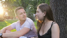 Guy and girl relaxed listening to music in the park sitting under a tree.  stock footage