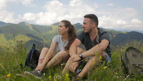 Guy and girl resting in the mountains against the background of clouds.  stock footage