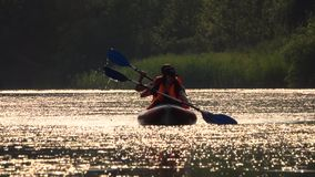 Guy and girl rowing along the river with paddles sitting in a kayak are sent to sunset. Slow motion stock footage