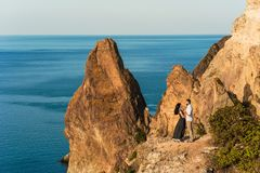 Couple in love by the sea hugging on the edge of the cliff royalty free stock photos