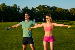 Guy with the girl shakes muscles  with dumbbells. Royalty Free Stock Image
