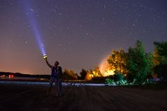 A guy with a girl shines a flashlight at the sky Stock Photography