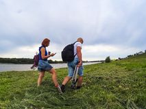 The guy and the girl in shorts and T-shirts go on high green grass on the river bank with backpacks. A woman has coffee and a stock photo
