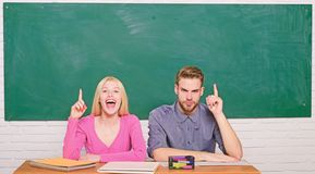 Guy and girl sit at desk in classroom. Correct answer on their mind. Studying in college or university. Apply for free. Program. Couple friends students stock images