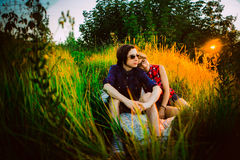 Guy and the girl sitting on a background of grass Stock Photo