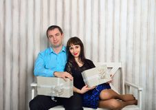 Couple with gifts sitting on a bench stock image