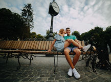 Guy and girl sitting on a bench Stock Photography