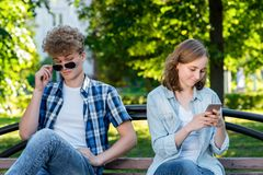 The guy and the girl are sitting on bench. Summer in nature. A girl in her hands holds a smartphone communicates in. The guy and girl are sitting on bench royalty free stock images