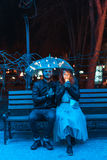Guy and girl sitting on a bench under an umbrella. On a night street Stock Images