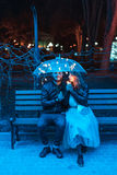 Guy and girl sitting on a bench under an umbrella. On a night street Royalty Free Stock Image