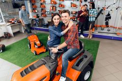 The guy and the girl are sitting on the lawn mower. stock photos