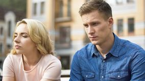 Guy and girl sitting next to each other, gloomy faces, first fight, relationship. Stock video royalty free stock images