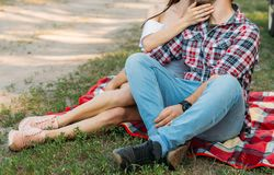 A guy and a girl are sitting on a plaid veil on the grass, hugging and kissing. a man in a plaid shirt and jeans, with a watch on. A guy and a girl are sitting stock image
