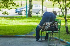 A guy with a girl sleeping on a bench outdoors royalty free stock image