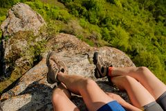 Guy and a girl in sneakers sit on a rocky mountain, dangling their legs down. Guy and a girl in sneakers and shorts sit on a rocky mountain, overgrown with stock photos