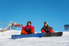 Guy and girl snowboarders sitting at top of ski slope stock photo