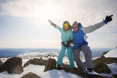 A guy and a girl snowboarders at the top of the mountain with th Stock Image
