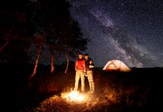 Guy and girl stand by fire with beer in their hands under the sky strewn with bright stars and milky way. Young couple - guy and girl hikers standing by campfire royalty free stock images