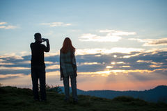 Guy and girl standing on the hill and photographed sunrise. Man and women tourists standing on the hill and photographed on phones sunrise. Rear view. Beautiful royalty free stock images