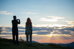 Guy and girl standing on the hill and photographed sunrise. Guy and girl standing on the hill and photographed on phones sunrise. Back view. Beautiful morning in stock images