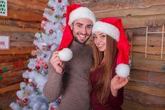 The guy with the girl standing together and holding the tips of the New Year`s hats royalty free stock image