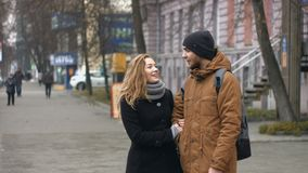 A young couple on a city street. The guy and the girl are standing together on a pedestrian street and talking cheerfully stock video