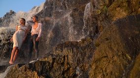 The guy and the girl are standing by the waterfall and watching the sunset. A wet guy and a girl are standing under a waterfall among the rocks and watching the stock video