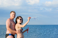 The guy and  girl start soap bubbles on the sea. Royalty Free Stock Photos