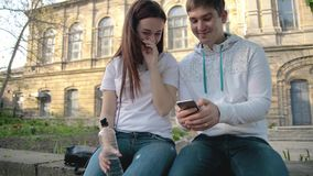 Guy and girl, students, sit in the park, shoot the video in the phone and laugh stock video