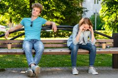 The guy with girl in summer on the bench. Conflicts in a relationship. The girl has a strong headache. Quarrels and royalty free stock photo