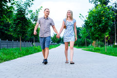 The guy with girl in a summer park holding hands walking relax, enjoy stroll, happy family concept slogan your text in Stock Photo