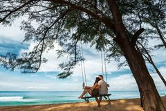 Couple in love on a swing by the sea. Couple in love on an island off the coast. Honeymoon. Couple by the sea. A guy and a girl travel to beautiful places royalty free stock photos