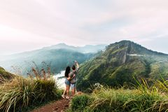 A loving couple taking pictures of the sunrise in the mountains. A guy and a girl taking pictures of the sunrise in the mountains Stock Photos