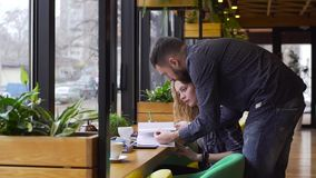 Slowmotion of guy and girl together prepare for the exam in a cafe. Guy and girl together prepare for the exam in a cafe stock footage