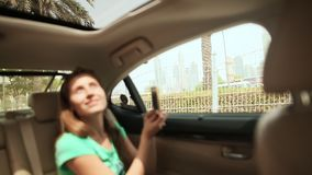 A guy and a girl travel in Dubai by car and admire the city. stock video footage