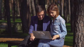 Guy and girl use pc outdoor. stock video