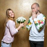 Guy with a girl on Valentine`s Day giving flowers. Fashion couple , smiling happily and surprised. Vogue Style, on Valentine`s Day Stock Photos