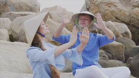 A guy and a girl in Vietnamese hats sit on rocks on the beach in a yoga pose, meditate and look at each other. Concept stock video footage