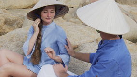 A guy and a girl in Vietnamese hats sit on rocks on the beach in a yoga pose, meditate and look at each other. Concept stock footage