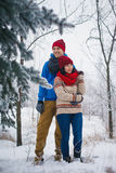 Guy and girl walk and have fun in the forest. In winter Royalty Free Stock Photography
