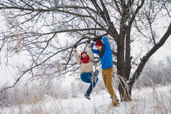 Guy and girl walk and have fun in the forest. In winter Stock Photos